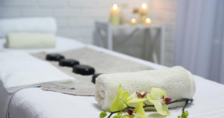 Bild eines Massageraumes mit Kerzen, einer Massageliege und Massage-Steinen